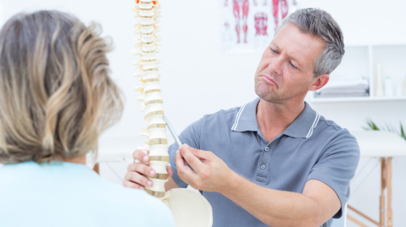 Physiotherapist showing spine model to his patient in medical office